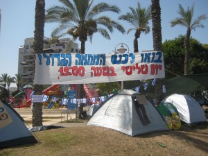 The 'tent city' housing protest site in Ashdod this morning; there are approximately 20 tents. The leftover sign from yesterday reads: Come to the protest Tuesday at 7:00 pm.