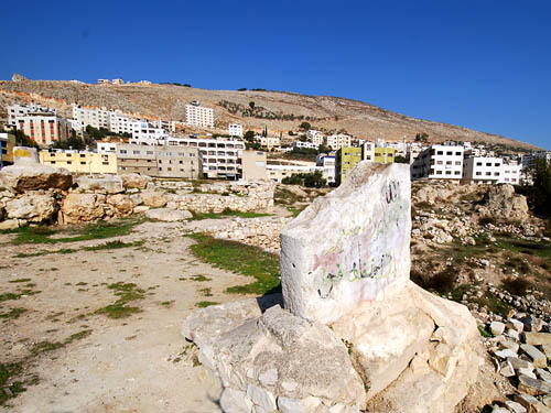 A sacred stone at the ruins of  Israelite Shechem (note the new city of Shechem--known by the Palestinians as 'Nablus' in the background. Also notice the Arabic graffiti on the stone--a type of vandalism taking place across Judea and Samaria and Palestinians attempt to 'Palestinize' Jewish history