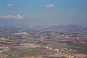 The site of Armageddon? The plains of Megiddo with the road to Afula running from the lower right of the frame to just below the center left.  Just above the center left you can see the S shaped road to Bet Shean heading east to the Jordanian border. Mount Gilboa looms to the right.