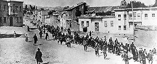 """Armenians on the """"Death March"""". Turkish soldiers with guns are in the foreground."""