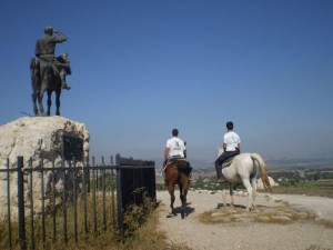 A mounted volunteer patrol passes by a memorial to Alexander Zeid, the founder of the first Hashomer.