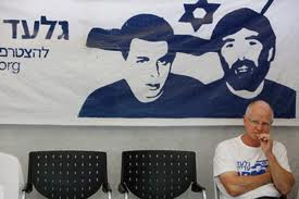 Gilad's father Noam sitting under a banner with pictures of Gilad Shalit and Ron Arad