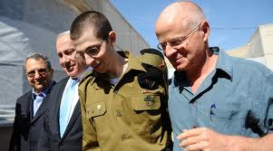 A gaunt and fragile Shalit manages a smile as he is propped up by Netanyahu and his father upon his arrival at Tel Nof Air Force Base yesterday.