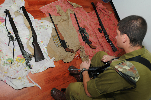 An Israeli soldier in Hebron looks over weapons of the type captured last night (photo source: http://www.flickr.com/photos/idfonline).