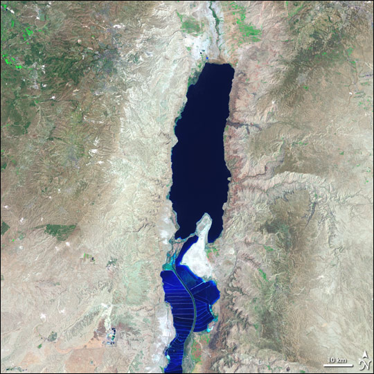 "An aerial view of the dying Dead Sea. Note the completely dried island in the middle and the mineral ""farming ponds"" in the bottom half of the ""Sea""."