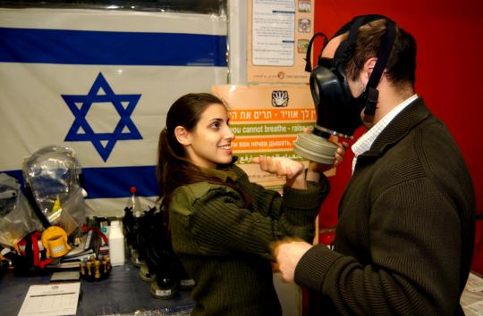 An IDF soldier shows a person how to use his new gas mask (picture: upi.com).
