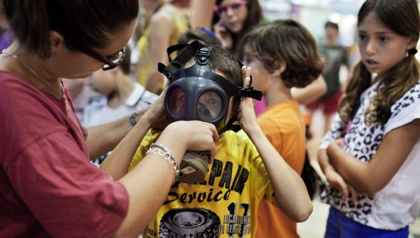 Israeli elementary school children being fitted for gas masks (photo: en.rian,ru).
