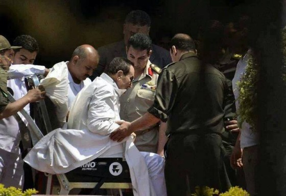 Mubarak being helped out off of his hospital stretcher so that he can get on a waiting military helicopter (photo: AFP).