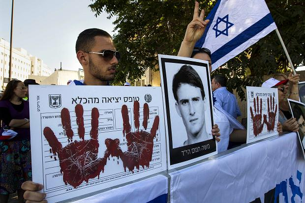 "A protest against the prisoner release in Jerusalem last week. The ""red hands"" indicate that each of the terrorists being released has ""blood on his hands"". The picture is of an Israeli who was murdered (picture source: Ronen Zvulun/Reuters)."