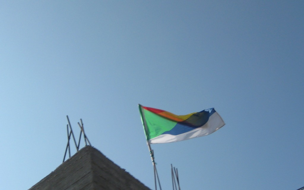 "A Druze flag flying over a building in Majdal Shams. Note the ""unfinished"" building--metal bars extending upward for another floor to be added to the house as the family grows."