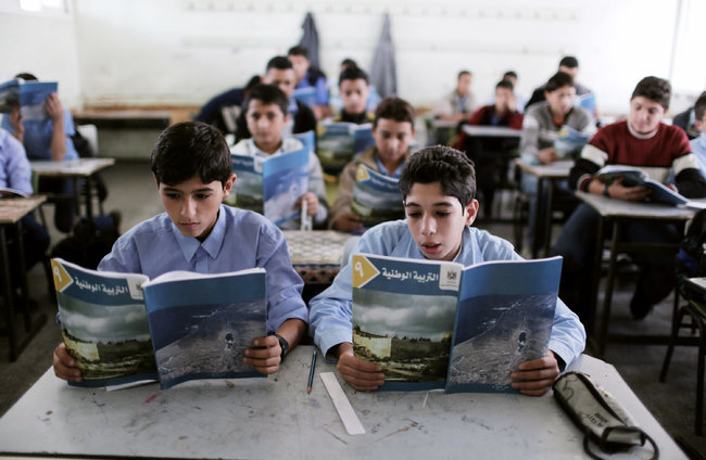 """Eighth graders in Gaza studying from their new """"textbooks"""" (picture source: Wissam Nassar for The New York Times)."""
