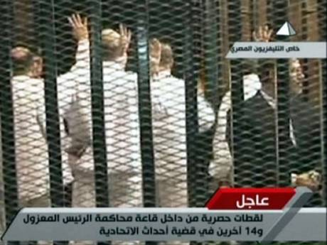 Morsi in the prisoner cage with his business suit (right side). His fellow Muslim Brotherhood defendants in prison garb refusing to face the court (picture source on photo).