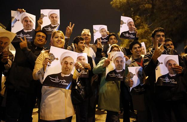 Some of the adoring multitude in Tehran yesterday with posters of Rouhani (picture: hurriyet).