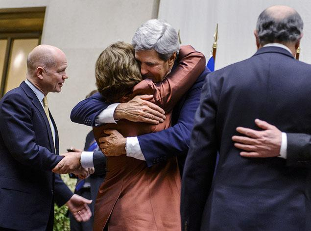 "There were hugs and kisses (that's John Kerry and Catherine Ashton in an intimate embrace) and smiles and handshakes (note British Ambassador William Hague on the left (Hague warned Israel yesterday not to do anything to upset the applecart) as the nuclear ""deal"" with Iran was signed. But apparently, there is more than one version of that deal (picture: Getty Images),"