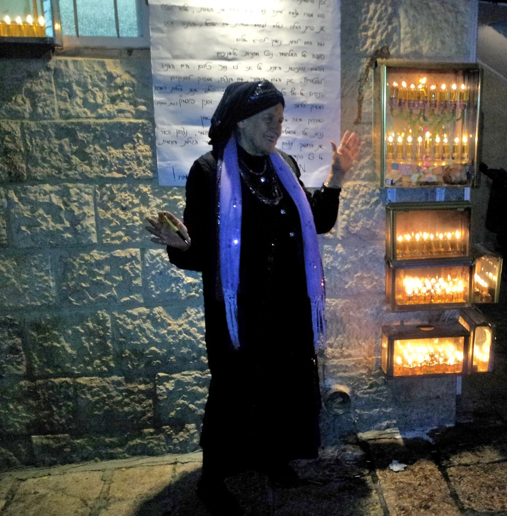 A woman outside her home in the Jewish Quarter just after lighting her Chanukiah.
