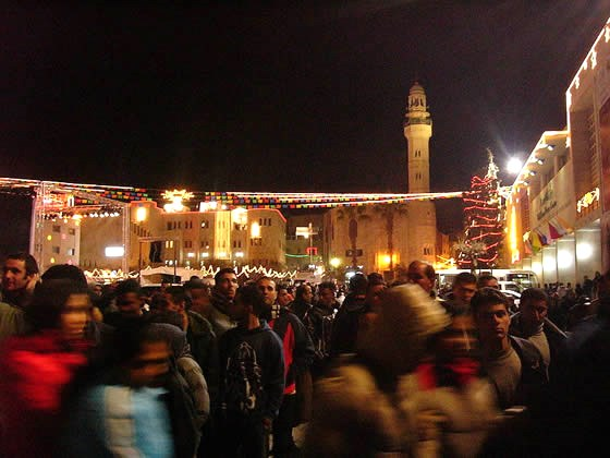 The scene in Bethlehem's Manger Square. Note the Christmas decorations and the Mosque of Omar looming over the Square (picture: israelseen).