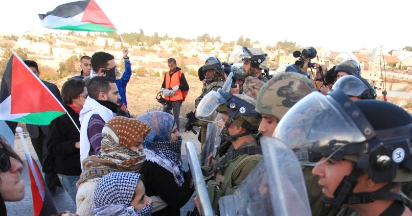 Note the standard form of protest--Arabs send their women out on the front line to spit at and curse passive Israeli soldiers. Also note the Palestinian flags being waved (picture: Times of Israel).
