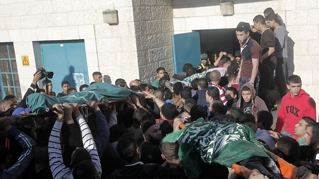 Three dead Palestinian terrorists being carried through the streets of Jenin this morning (picture: AFP).