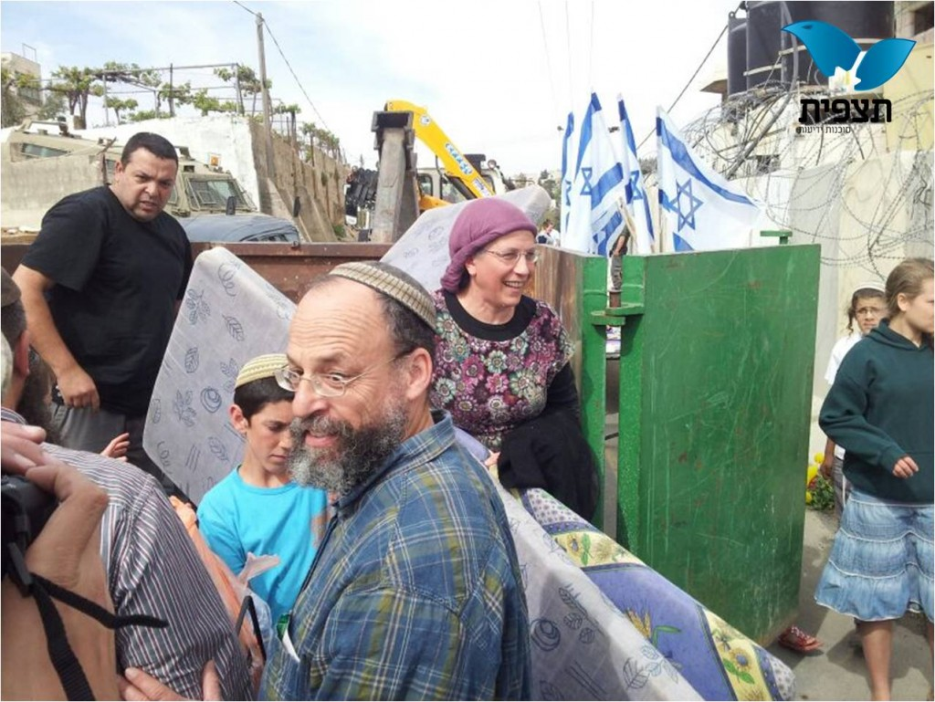 The happy families began moving in today; the woman in the center is Orit Struck (picture source on picture: Observation Agency).
