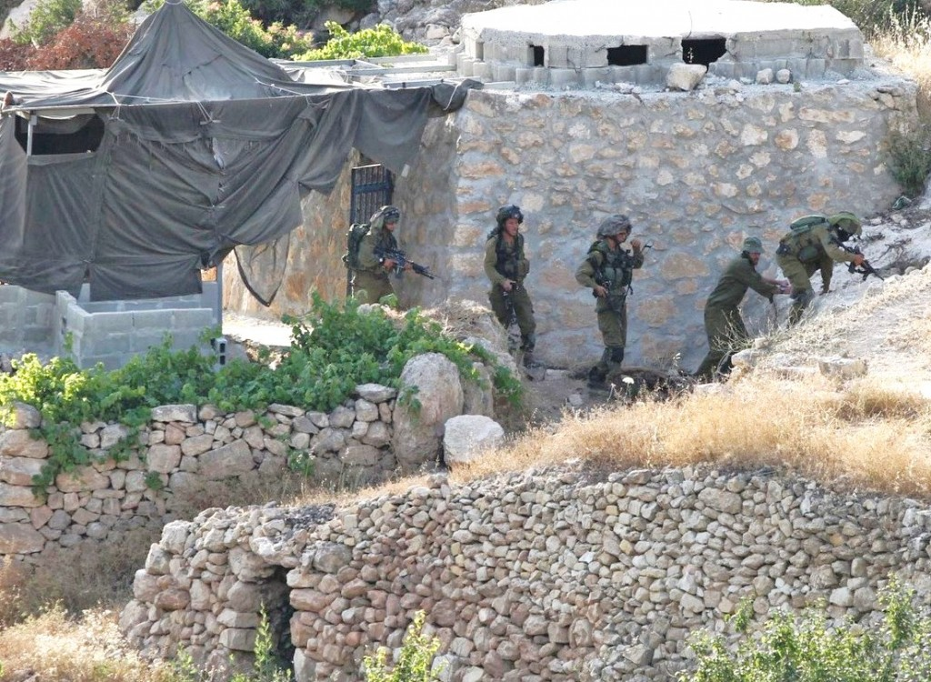 Look carefully at this picture of Israeli soldiers working their way through a tiny section of Hebron. Note how the last soldier is looking up. Note the end of tunnel structure in the lower left of the photo and what looks almost like a pillbox bunker above the soldiers.