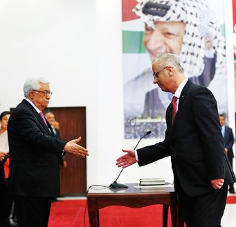 Mahmoud Abbas (left) signing in Rami Hamdallah as new head of the PLO-Hamas terrorist government under the watchful eye of Abbas' mentor Yasser Arafat (photo: Reuters).
