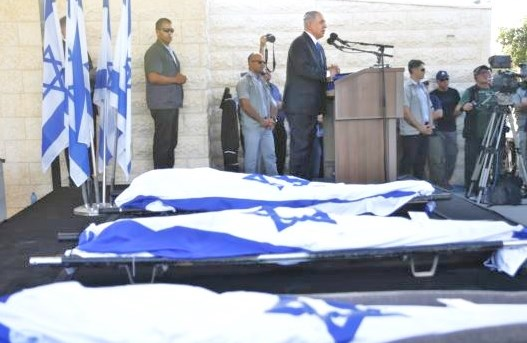 PM Netanyahu speaks at the funeral in Modi'in yesterday beside the remains of the three teenagers (Photo: AP).
