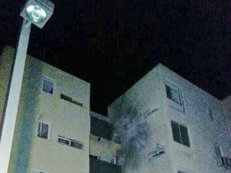 A picture taken last night in a darkened Sderot of an apartment building struck by a missile.