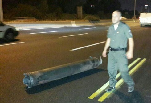 An Israeli policeman stands beside a missile that hit a road near Tel Aviv last night.