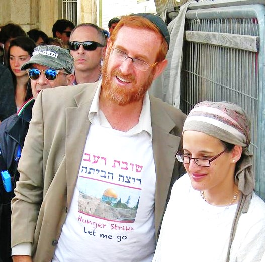 Rabbi Yehuda Glick waiting in line at the entrance to the Temple Mount. Always identifiable because of his height and his red hair, Glick is wearing a shirt that calls attention to the hunger strike that he engaged in to protest government policy concerning Jews on the Mount.