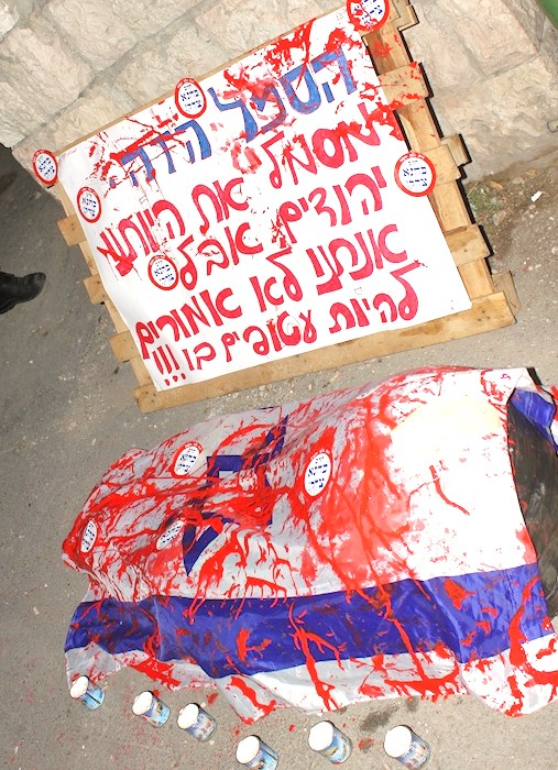 """The gist of the caption is that the flag of Israel which is a symbol of pride for Jews is being used these days to wrap the bodies of Jewish victims. Again, the small circular signs read """"Rabbi Kahane was right."""""""