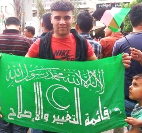 The terrorist proudly holding a Hamas flag.