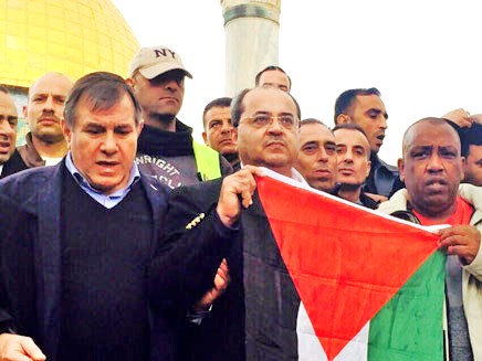 Ahmed Tibi in center (wearing glasses)--holding a Palestinian flag on the Har HaBeit in front of Judaism's holiest place (under the Kipat HaSela--the Dome of the Rock).