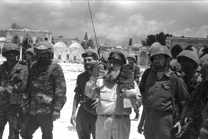 Rabbi Shlomo Goren (center) blowing the shofar and carrying a Torah in his left hand, and a bearded General Mordechai Gur (to his right) on the Temple Mount on June 7, 1967).