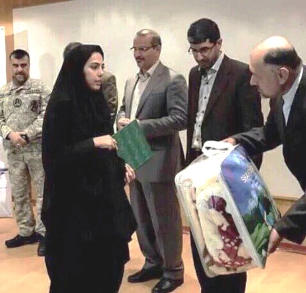 """A grieving family member receives a blanket. The question being asked by Iranians: """"Is a blanket all our sons are worth?"""""""