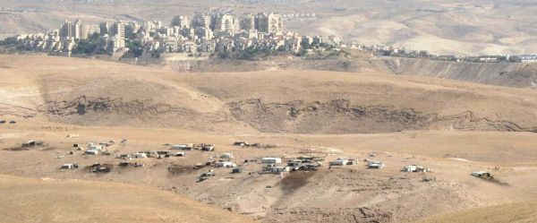 Note the scattered buildings of a new Palestinian settlement in the foreground and Ma'aleh Adumim in the background.