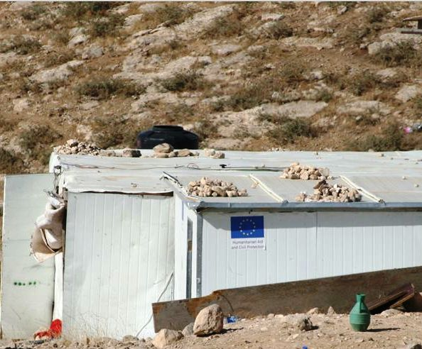 """Note the blue EU flag on the building with the words """"humanitarian aid"""" underneath."""