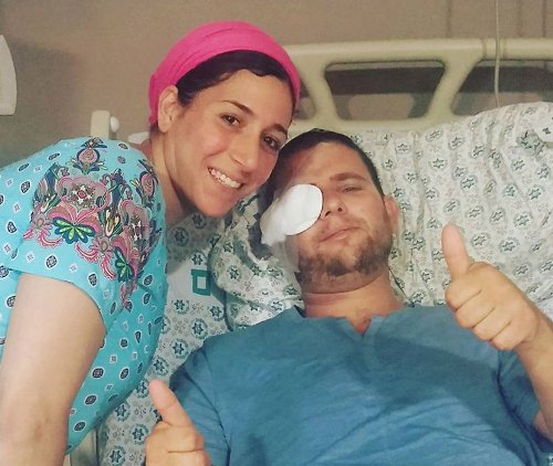 Shuki Gilboa giving the thumbs up in the hospital yeserday. With him is his wife.