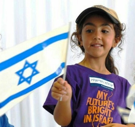 A new citizen of Israel who arrived at Ben Gurion airport yesterday (see story below). Note what is written on her shirt. (Picture: Walla).