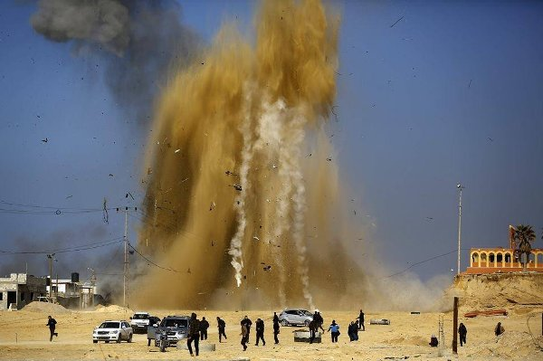 Hamas members running away from the site of an IDF attack this afternoon (AFP).