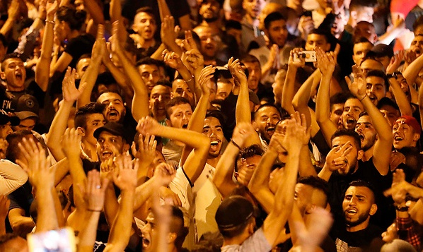 "The scene on the Palestinian street last night as candy was given out and Palestinians chanted ""Death to Israe."" (picture AFP)."