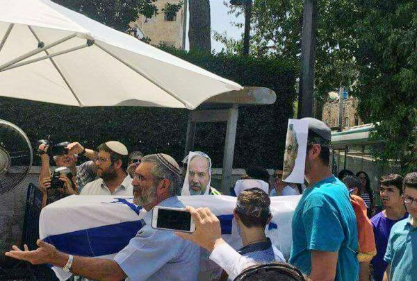 "Note that one of the demonstrators is wearing the face of ""Defense"" Minister Lieberman, and another the face of Netanyahu."