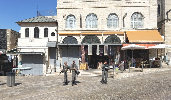 Just inside the Jaffa Gate. Note (left to right): the entrance to the Muslim Quarter, the shuttered Muslim stores, the Border Policemen standing back to back for protection, and the road leading to the right to the Armenian Quarter.
