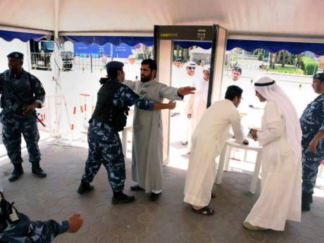 Muslim worshipers going through a metal detector at the Grand Mosque in Kuwait.