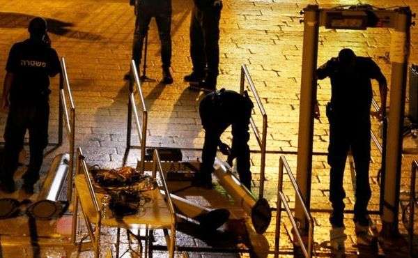 Kowtowing to King Abdullah of Jordan, Israeli workers remove the metal detectors in the middle of the night last night (photo: Reuters).