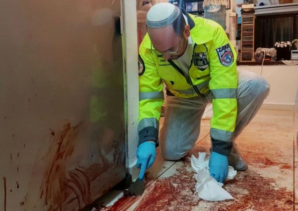 A member of Zaka scraping the blood of the Salomons off of the floor. Zaka volunteers come to such scenes to recover human remains so that the dead can be assured a proper burial in accordance with Jewish law (photo: Jerusalem Post).