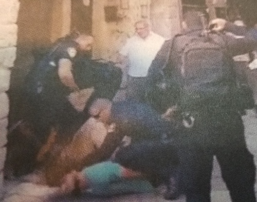 In this grainy photo taken from the video, you can see a policeman with his knee in the back of a Jewish man lying on the ground.