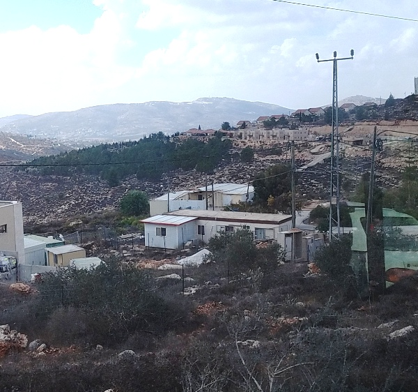 Look closely here. This camera shot is from the road that leads out of Itamar in the opposite direction from the road that leads in. In the foreground, you see some caravan/prefab homes; in the far background, you see a cluster of houses, the first one of which the Fogels lived in.