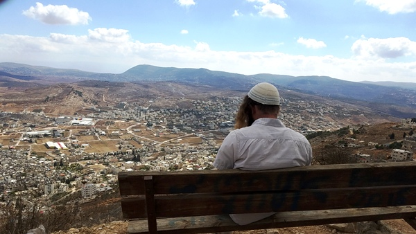 I took this picture of a young religious man reading his Torah (which you cannot see) on a bench near Joseph's Outlook. That is Shechem that you see in the valley.