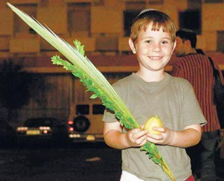 A proud Israeli boy holding his lulav (the long green frond) and his etrog (the yellow lemony looking fruit).
