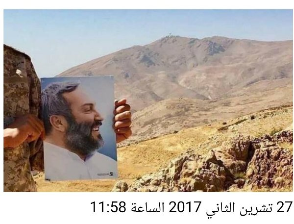 A Hezbollah fighter is holding a picture of